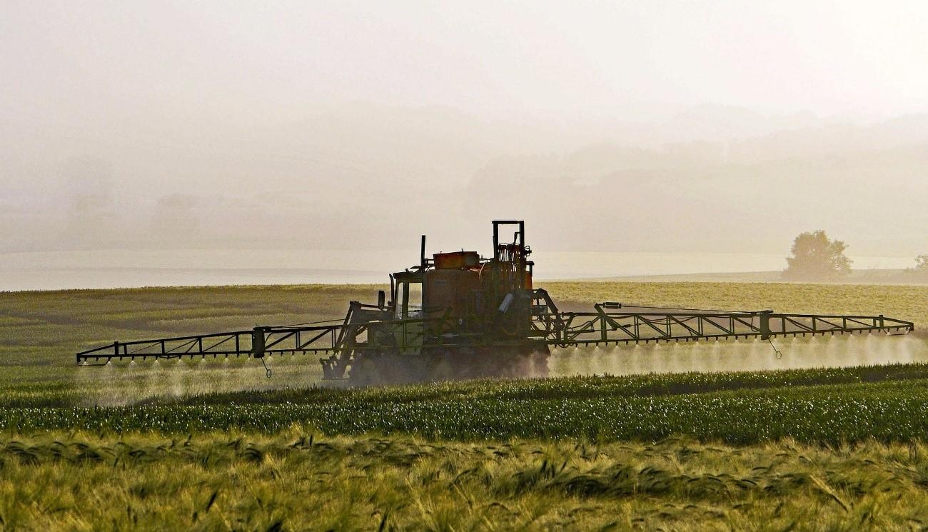 Tractor aplicando pesticidas en zona de cultivo